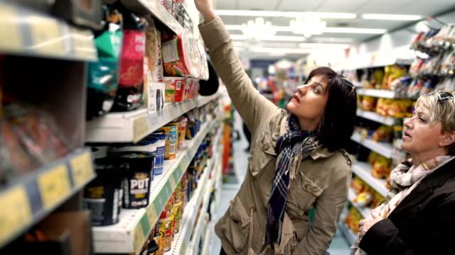 vidéos et rushes de vente, shopping, consumérisme et concept de personnes-deux femmes d'âge mûr au magasin d'épicerie ou au supermarché - 50 54 ans