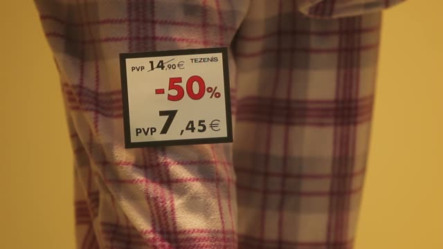 A sale sign is displayed in the window of a store on the first day of sales in Madrid Spain on Tuesday Jan 7 A discount label is fixed to clothes on...