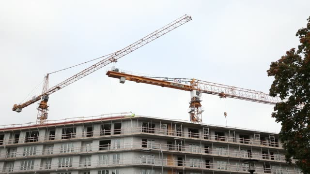 A sale sign points the way to real estate properties for sale in Stockholm Sweden on Monday Oct 19 Construction cranes stand above a new development...