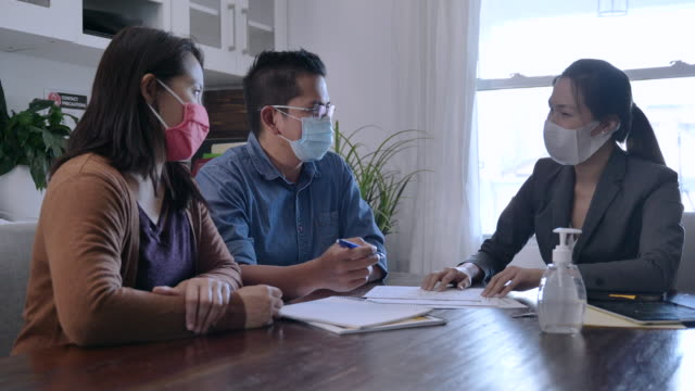 vídeos y material grabado en eventos de stock de agente de ventas reunido con pareja mientras usa máscaras - propiedad inmobiliaria