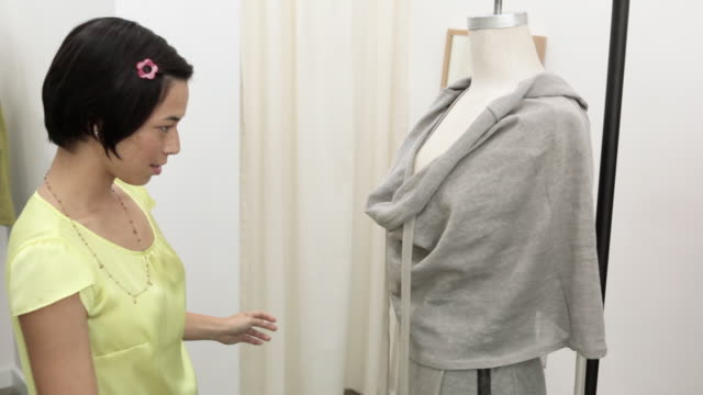 sales assistant adjusting clothes on a mannequin - mannequin stock videos & royalty-free footage