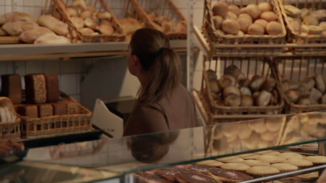 ms sales assistant sell bread to custumer / copenhagen, seeland, denmark    - bread stock videos & royalty-free footage