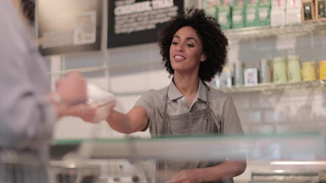 vidéos et rushes de sales assistant serving customer at a deli counter - service