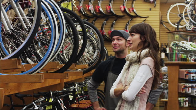 ms sales clerk assisting young woman in bike shop / portland, oregon, usa - store stock videos & royalty-free footage