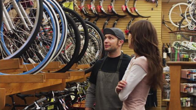 ms sales clerk assisting young woman in bike shop / portland, oregon, usa - portland oregon bike stock videos & royalty-free footage
