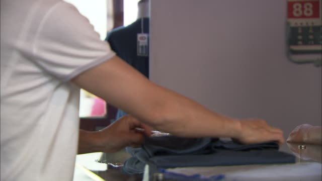 cu sales clerk folding t-shirt at checkout counter, beijing, beijing, china - shirt stock videos & royalty-free footage