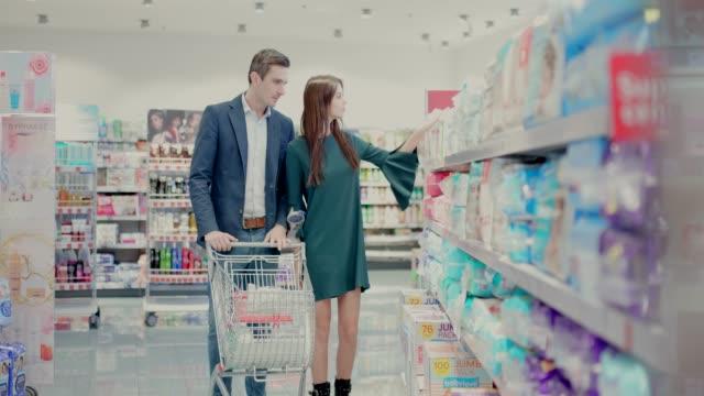 vídeos de stock e filmes b-roll de sales clerk helping couple in shopping for diapers - fralda