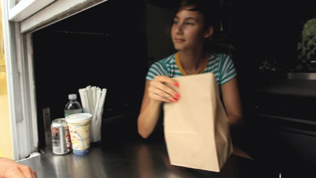 ms pan sales clerk in concession stand handing out food bag to customer / jersey city, new jersey, usa - take away food stock videos and b-roll footage