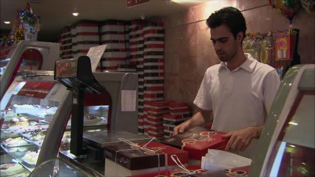 cu sales clerk packing cakes into cardboard boxes in confectionary, north tehran, iran - skåp med glasdörrar bildbanksvideor och videomaterial från bakom kulisserna