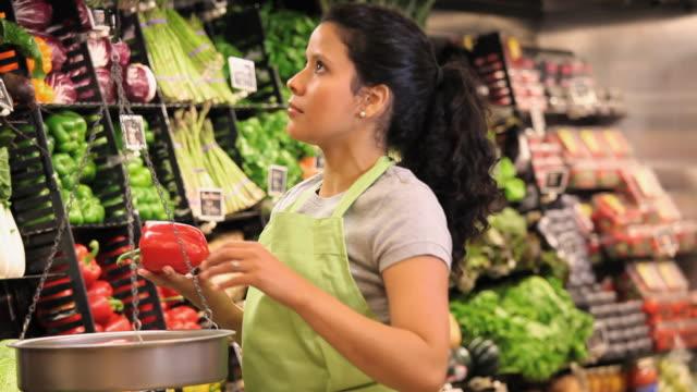 vídeos y material grabado en eventos de stock de ms sales clerk weighing bell peppers on scales in grocery store / richmond, virginia, usa - cabello recogido