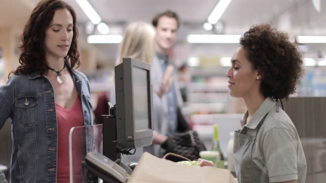 sales clerk working at grocery store - checkout stock videos & royalty-free footage