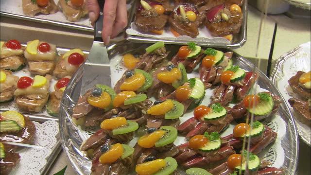 cu sales clerk's hand taking appetizer from tray at dallmayr, luxury delicatessen, munich, bavaria, germany - 盆点の映像素材/bロール
