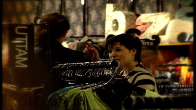 vidéos et rushes de sales of ecologically sound clothing ranges rise speeded up sequence of women trying on various tops in clothes shop / clothes racks / shelves of... - présentoir