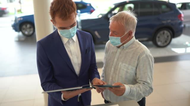salesman and customer looking at catalog in car dealership - salesman stock videos & royalty-free footage