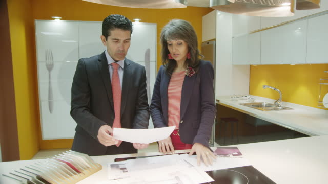 TS LA MS salesman and female client discussing  plans  in a kitchen showroom showing modern furniture