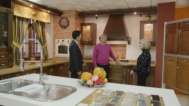 WS salesman and mature couple in kitchen showroom with traditional furniture; they discuss the exhibit and laugh