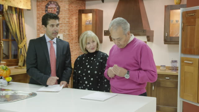 ms salesman and mature couple signing contract in kitchen showroom displaying traditional furniture - signature stock videos & royalty-free footage