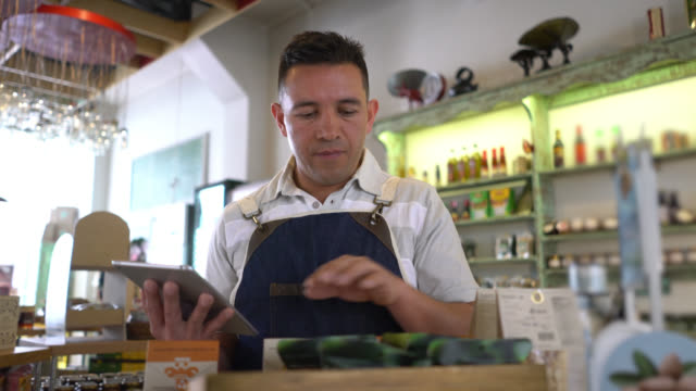 salesman at a food store doing an inventory of the products using a tablet looking very focused - apron stock videos & royalty-free footage