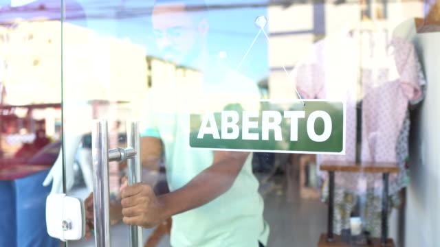 vídeos de stock, filmes e b-roll de vendedor que fecha a loja de roupa - loja