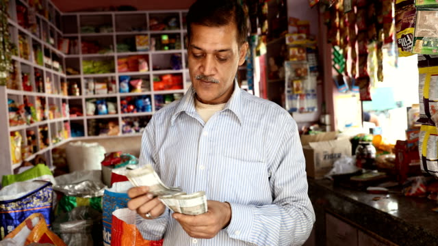 ms salesman counting money while standing in shop / delhi, india - wages stock videos & royalty-free footage