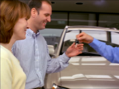 pan salesman giving car keys to couple, shaking hands - selling stock videos & royalty-free footage