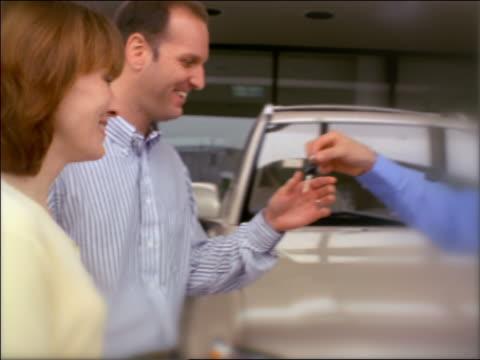 SELECTIVE FOCUS PAN salesman giving car keys to couple, shaking hands