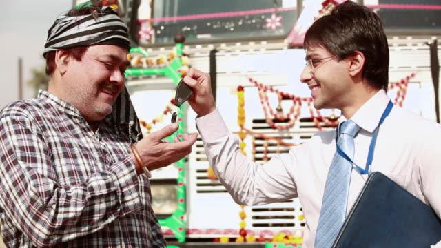 Salesman giving keys to a truck driver, Ballabgarh, Haryana, India