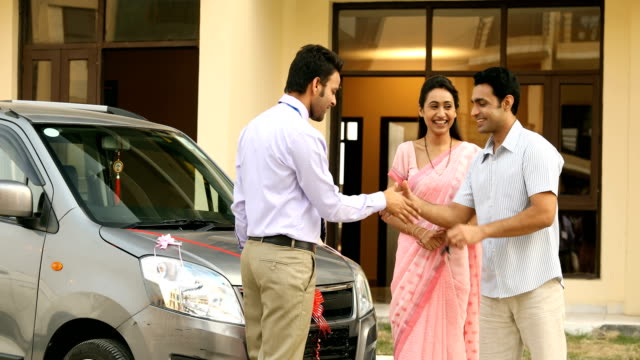 MS PAN Salesman handing over keys of new car to couple / Sonipat, Haryana, India
