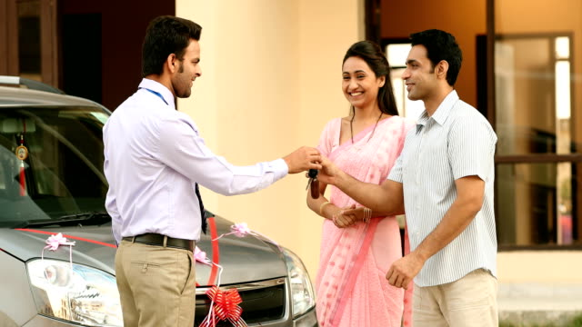 MS Salesman handing over keys of new car to couple / Sonipat, Haryana, India
