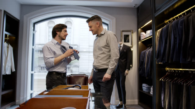 salesman helping male customer suggesting a necktie and a button down shirt to male customer - dressing up stock videos & royalty-free footage
