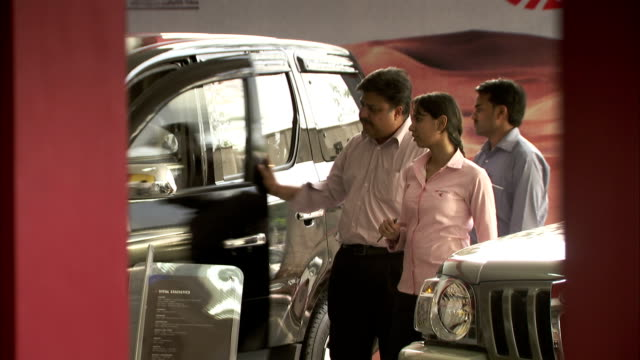 a salesman helps a couple examine a new car on the mahindra showroom floor. - car showroom stock videos & royalty-free footage