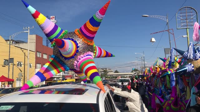 """salesman installs a giant """"pinata"""" on the roof of a customer s car at the """"jamaica"""" market on december 13, 2020 in mexico city, mexico. despite... - papier点の映像素材/bロール"""