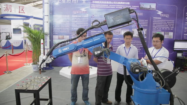 ms salesman introducing robotic arms to customer in exhibition / xi'an, shaanxi, china  - 展覧会点の映像素材/bロール