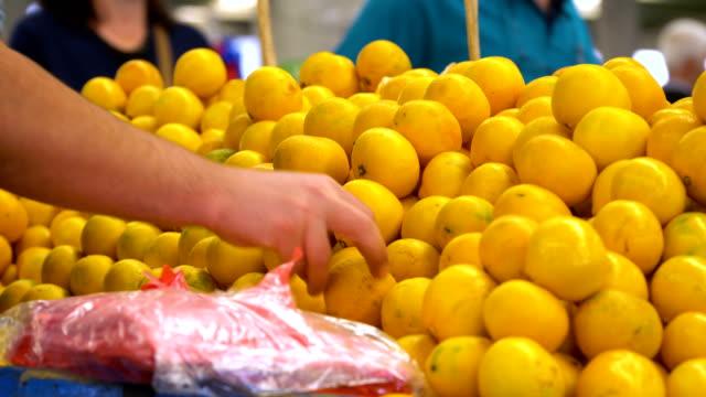 salesman is putting tangerines in line - greengrocer stock videos & royalty-free footage