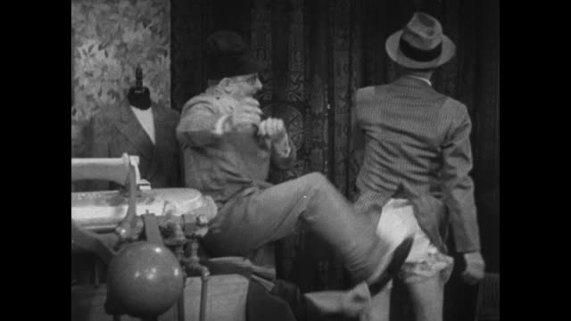1934 salesman kicks grouchy pantless tailor shop customer in the behind - sparka bildbanksvideor och videomaterial från bakom kulisserna