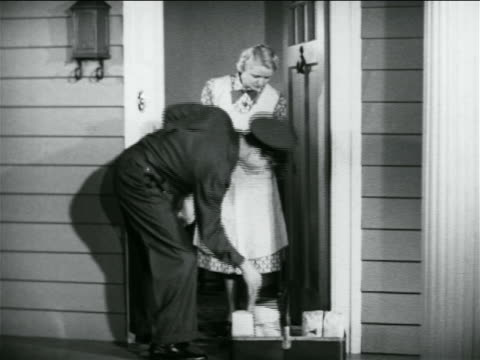 b/w 1938 salesman pointing to basket of items while talking to housewife in doorway / industrial - door to door salesperson stock videos & royalty-free footage