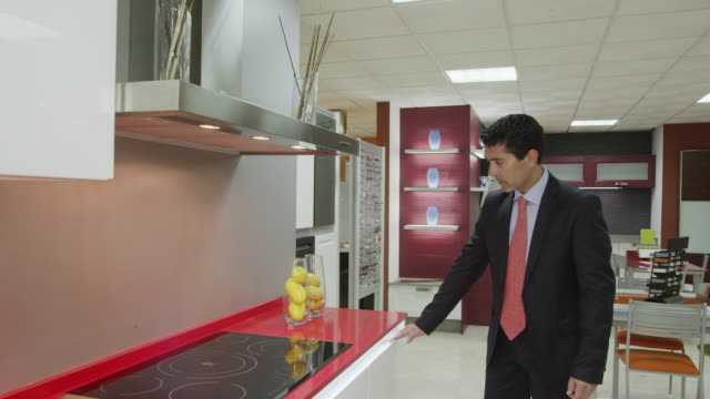 vídeos de stock e filmes b-roll de pov ts salesman showing kitchen furniture in showroom - vendedor comércio