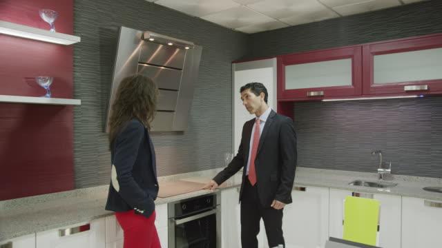 salesman showing kitchen furniture to young female customer - strategia di vendita video stock e b–roll