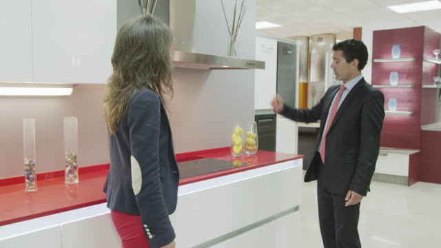 TS salesman showing kitchen furniture to young female customer