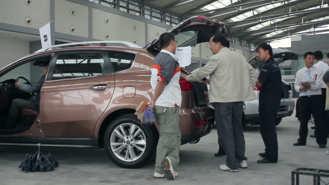ms salesman showing new car to interested customer inside showroom/xian,shaanxi,china - venditore video stock e b–roll
