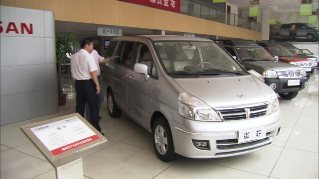 vídeos de stock e filmes b-roll de ws salesman showing new suv to interested customer inside showroom, beijing, beijing, china - stand de carros