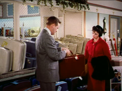 1962 salesman showing piece of luggage to woman in store / industrial