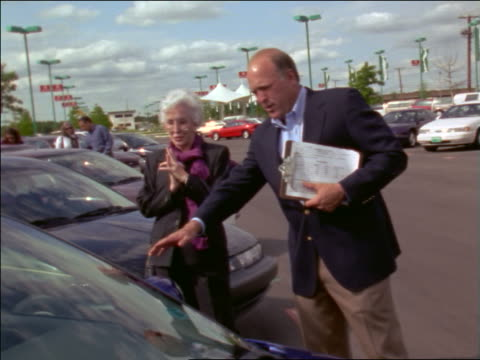 stockvideo's en b-roll-footage met salesman showing senior woman new cars in lot - toonzaal