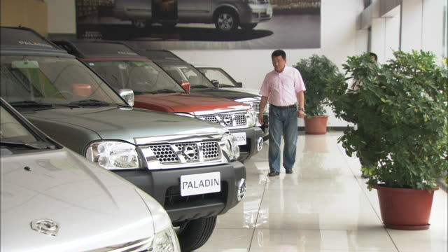 ws salesman showing various cars to customer in showroom, beijing, beijing, china - sports utility vehicle stock-videos und b-roll-filmmaterial