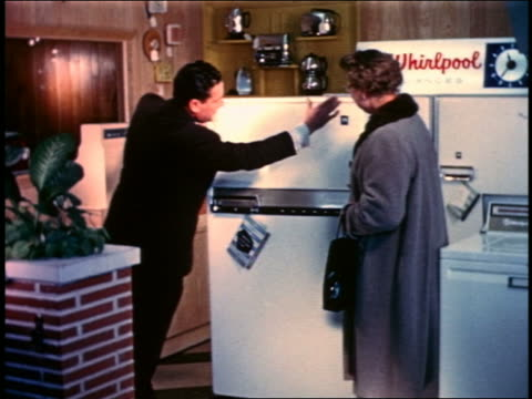 1958 salesman showing woman Whirlpool refrigerator in showroom
