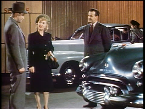 1948 salesman smiles at couple talking and looking at oldsmobile in showroom / industrial - selling stock videos & royalty-free footage