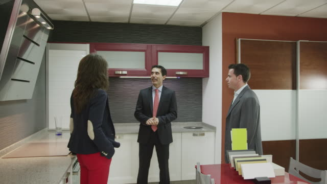 salesman talking to young couple in kitchen furniture showroom