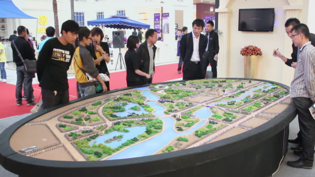 ws salesman talking with customer in housing exhibition/xian,shaanxi,china - 展覧会点の映像素材/bロール