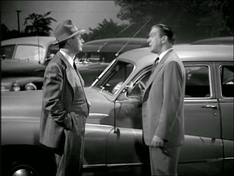 B/W 1950 salesman talks + shows car to man in car dealership lot