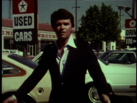 1978 ms salesman walking through used car lot talking about safety belts / united states - 1978 stock-videos und b-roll-filmmaterial